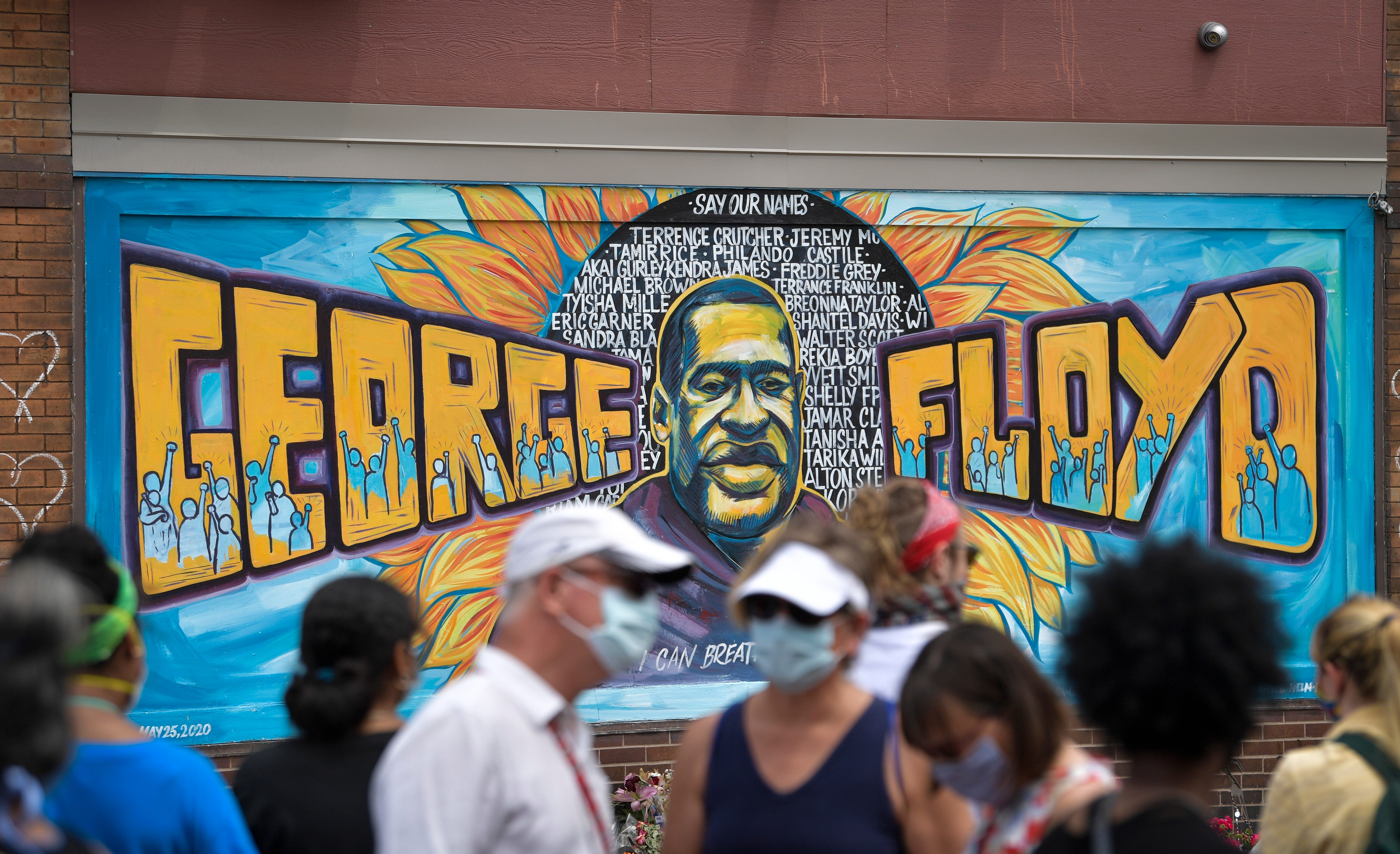 A crowd of people walk past a colorful mural of George Floyd in Minneapolis.