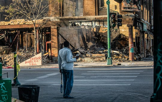 A man looks at the destruction of businesses along Lake Street in Minneapolis on Sunday.