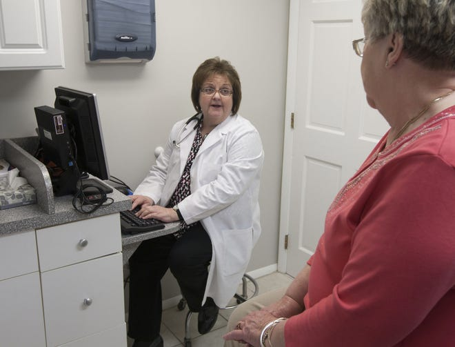 Diane Verga, a physician with Hooper Avenue Adult Care in Toms River, N.J., checks patient Carol Nering's electronic medical record on March 25, 2013.