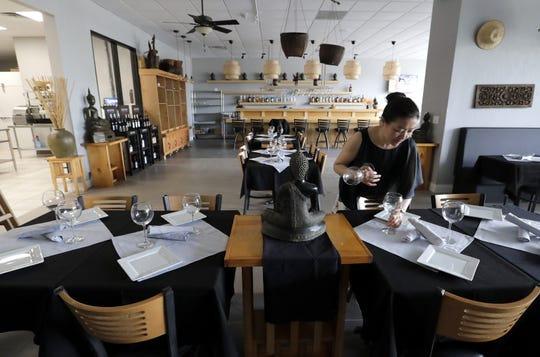 Bartender Penny Fan places wine glasses and silverware on tables at the new Thai Ginger Bistro restaurant in Appleton.