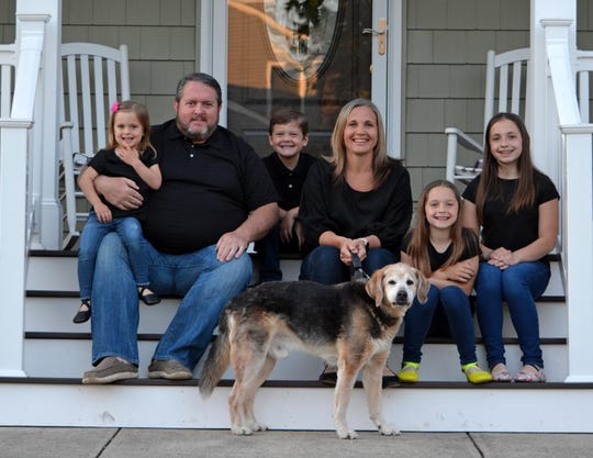 """At this point, you have to laugh about everything because it just keeps going and going,"" said Tara Paulson, shown with her family on the porch of their Ocean Township home. From left are Charlotte, Erik,  Ryland, Tara, Kadence, Addison, and dog Jack."