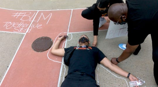 A chalkline is drawn in chalk around Elijah Barnes, Bayville, during a protest outside the Hall of Records in Freehold Borough, NJ, Tuesday, June 2, 2020.  People had gathered there to protest against the death of George Floyd at the hands of Minneapolis Police.