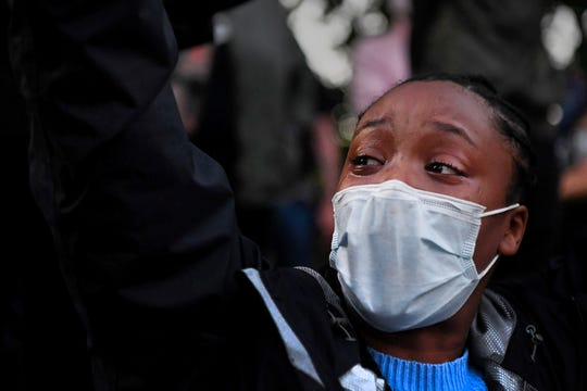 """Tears stream down Jahni Gilliland's face as she chants with her hands in the air across the street from the Asheville Police Department June 1, 2020. When asked how she was feeling, Gilliland choked up and replied, """"The same way I've felt my whole life."""""""