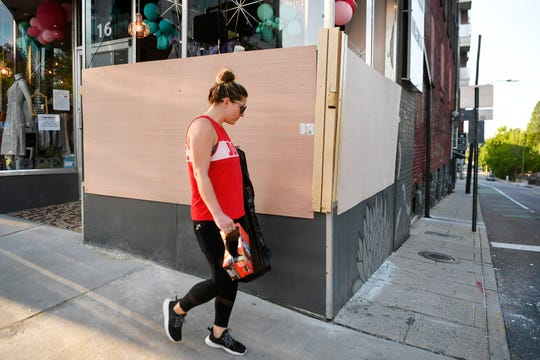 """Raychel Ragsdale cleans up around the Hazel Twenty boutique June 2, 2020. """"I know the owner and wanted to help out,"""" she said."""