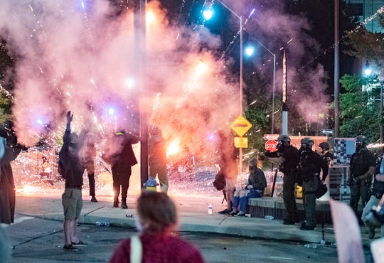 Fireworks explode as police shoot tear gas and rubber bullets at protestors during a second night of protesting in downtown Asheville in response to the killing of George Floyd, who is black, by a white police officer in Minneapolis on June 1, 2020.