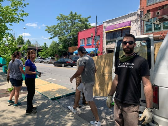 Volunteers help board up businesses in downtown Asheville June 2.