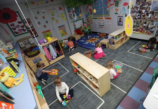 Youngsters at Noah's Ark Daycare in Port Orchard play with their toys while staying inside their socially-distanced squares on Tuesday.