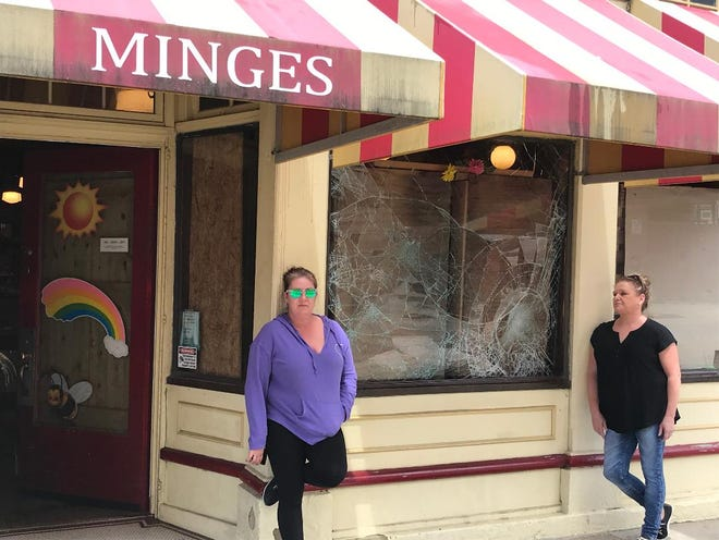Store manager, Heather Rhor, left, and owner, Ruthie Ochs, stand outside a broken window Monday at Peter Minges & Sons candy store Downtown