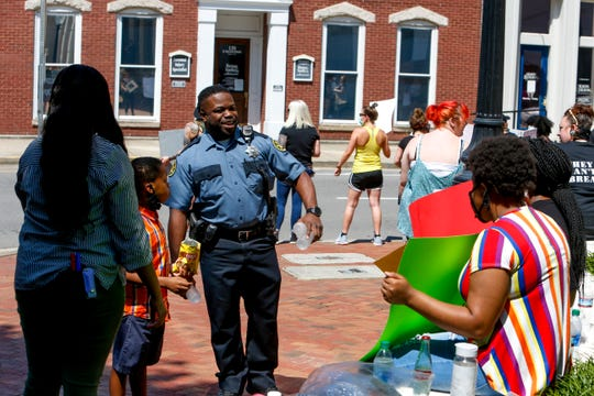 A Montgomery County Sheriff's deputy visits family attending the demonstration at a protest for justice over the death of George Floyd at the Montgomery County Historic Courthouse in Clarksville, Tenn., on Tuesday, June 2, 2020.