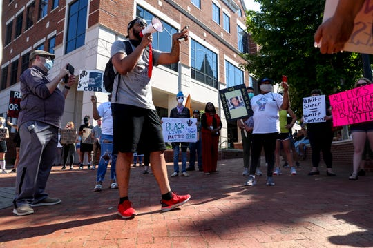 Keith Howard, a local public speaker, speaks with a megaphone to people that gathered at a protest for justice in the death of George Floyd at the Montgomery County Historic Courthouse in Clarksville, Tenn., on Tuesday, June 2, 2020.