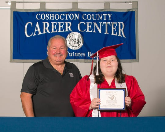 Tad Johnson of the Coshocton County Career Center's Board of Education awards Jessie Ruby with the Outstanding Career Center Student of the Year Award for the 2019 to 2020 school year at a Career Passport ceremony held at the vocational school to honor seniors. Ruby was a student in the culinary arts program.