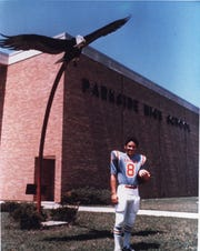Tony Dungy in his Jackson Parkside High School uniform   in front of the school where he played high school football.