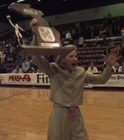 Birmingham Marian coach Mary Lillie Cicerone with the state championship trophy after beating Saginaw Arthur Hill in the Class A final on Dec. 5, 1998.
