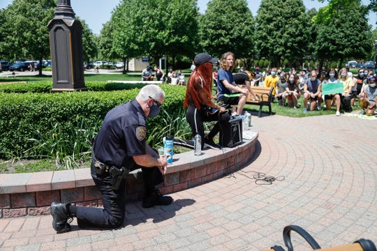 John Kosanke, Grosse Pointe Woods police chief kneel in solidarity with December Robinson of Grosse Pointe Woods and more 100 protester outside of the Grosse Pointe Woods city hall and public safety office, Tuesday, June 2, 2020.