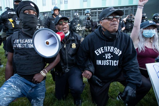 Detroit Police Deputy Chief Todd Bettison, center, takes a knee along with Rev. W.J. Rideout III, right, and protesters in front of the Detroit Police headquarters in Detroit, Sunday, May 31, 2020. Bettison asks people to go home.