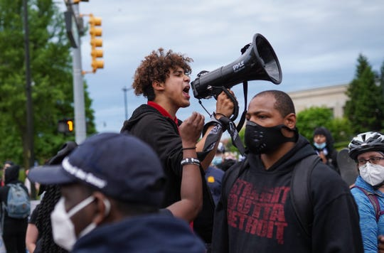 Stefan Perez of Detroit talks with protesters at the end of a protest march Monday through the city.