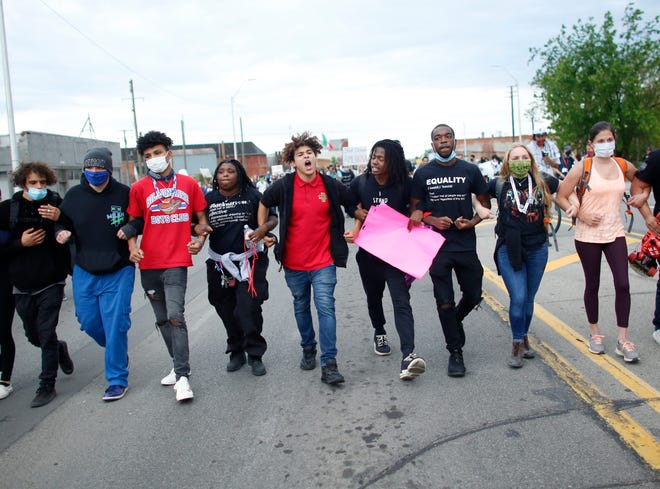 Stefan Perez, of By Any Means Necessary, center in red shirt, marches with demonstrators through southwest Detroit to protest against police brutality and the death of George Floyd on Monday, June 1, 2020.