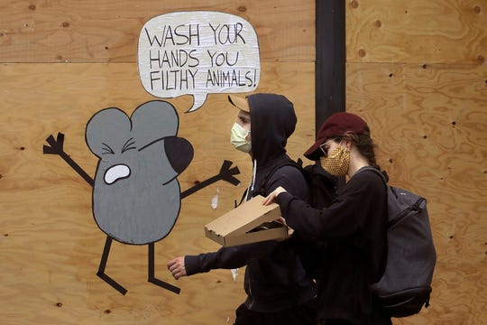 In this May 2, 2020, file photo, a man and woman wearing masks to prevent the spread of the coronavirus walk past a cartoon advising people to wash their hands on a boarded up storefront in San Francisco.