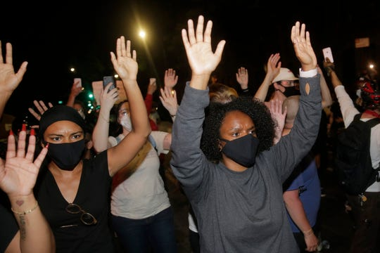 Protesters hold their hands in the air in the Brooklyn borough of New York, Saturday, May 30, 2020.