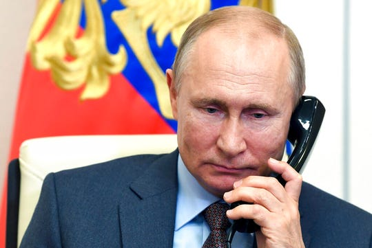 Russian President Vladimir Putin speaks on the phone during a meeting with Russian Prime Minister Mikhail Mishustin via teleconference at the Novo-Ogaryovo residence outside Moscow, Russia, Tuesday, June 2, 2020.