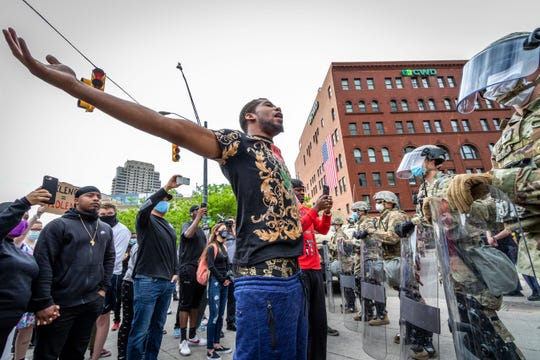 A protester shouts and raises his hands in front of the Michigan National Guard in downtown Grand Rapids on Monday.