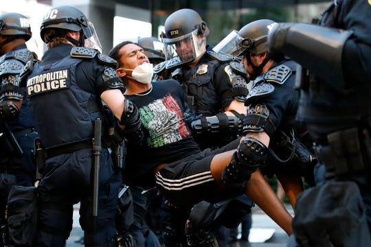 A demonstrator is taken into custody by police after a curfew took effect during a protest over the death of George Floyd, Monday, June 1, 2020, near the White House in Washington. Floyd died after being restrained by Minneapolis police officers.
