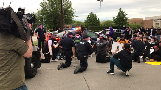 Troy police officers kneel with demonstrators on Coolidge Highway at the end of a march on Monday.