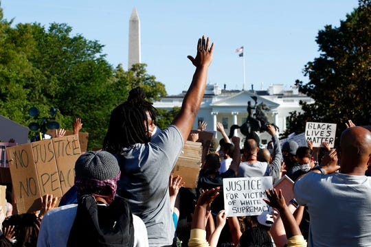 Demonstrators gather in Lafayette Park to protest the death of George Floyd, Monday near the White House in Washington. Floyd died after being restrained by Minneapolis police officers.