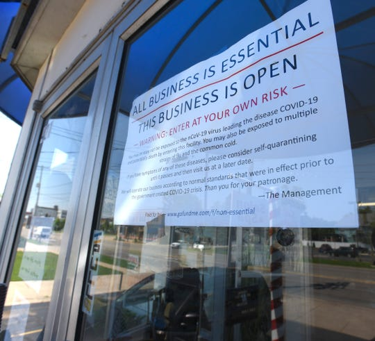A sign in the window of Karl Manke's barber shop proclaiming all business is essential.