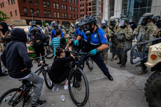 Police use bicycles to move back protesters back after the curfew Monday in downtown Grand Rapids.