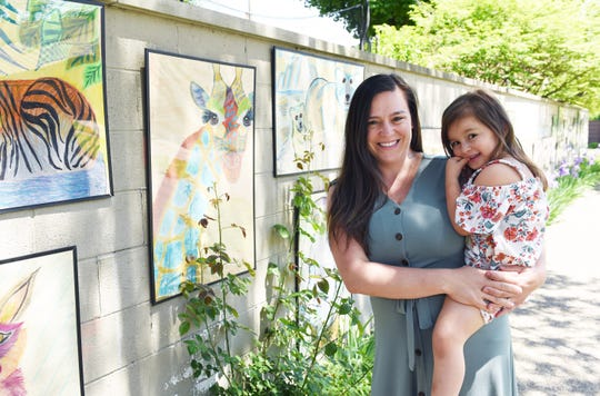 Frankie Piccirilli, 39, owner and artist of the Social Distance Zoo, poses for a photo with her daughter Giselle, 3, Tuesday, June 2, 2020. Piccirilli's Social Distance Zoo is a series of 24 paintings of animals that she created and has displayed on a brick retaining wall outside her home. It's become an attraction for neighbors and passers-by.