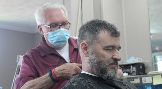 Owosso barber Karl Manke cuts Randy Hamilton's hair on Tuesday, June 2, four days after a court ordered him to cease all operations at his shop.
