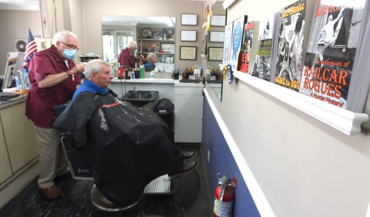 Owner Karl Manke, left, cuts the hair of Mike Calhoun, of Owosso, Tuesday afternoon, with books, written by the barber, on display on the wall.