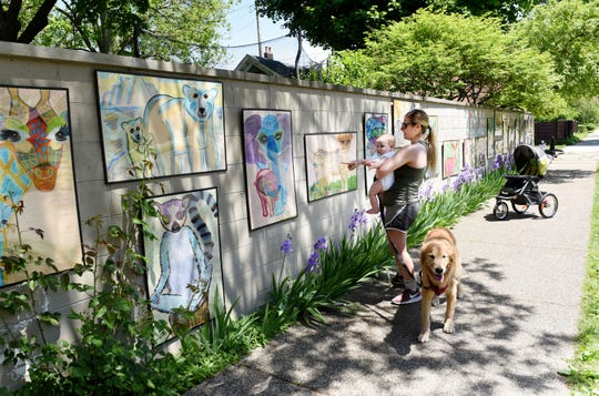 Lea Hunt, 30, of Detroit and her 9 month old son Homer views the Social Distance Zoo wall, Tuesday, June 2, 2020. Frankie Piccirilli's Social Distance Zoo a series of 24 paintings of animals that she created and has displayed on a brick retaining wall outside her home.