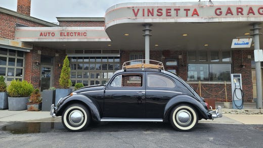 The 1964 VW Bug's distinctive profile in front of the classic Vinsetta Garage on Woodward Avenue, Royal Oak.
