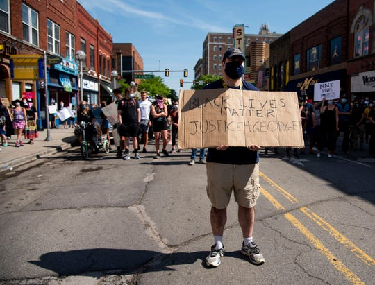 A demonstrator holds up a sign while standing in the middle of State Street during a peaceful protest in Ann Arbor on Tuesday, June 2, 2020. Ann Arbor police chief Michael Cox and other officers walked with demonstrators.