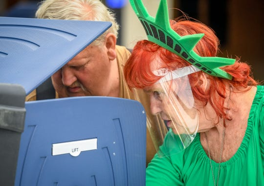 Dressed as the Statue of Liberty, lead election judge Jan Rhodes helps Mike Minnette with his ballot as voters exercise their rights at the Washington Square Mall voting center for the primary election, rescheduled because of the coronavirus pandemic Tuesday, June 2, 2020.