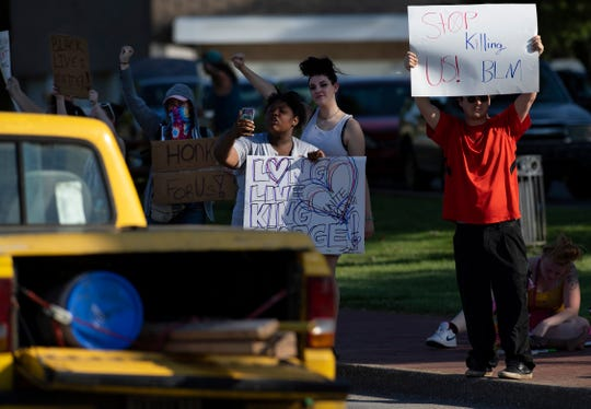 Protesters display signs to passing motorists at a staged protest for George Floyd on Riverside Drive near the Pagoda in Evansville Monday afternoon, June 1, 2020.