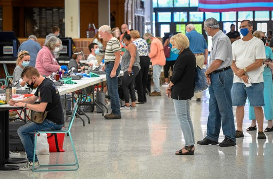 Lining up, voters exercise their rights at the Washington Square Mall voting center for the primary election, rescheduled because of the coronavirus pandemic Tuesday, June 2, 2020.
