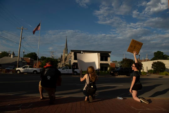 Protesters take a knee during a staged protest for George Floyd on Riverside Drive near the Pagoda in Evansville Monday afternoon, June 1, 2020.