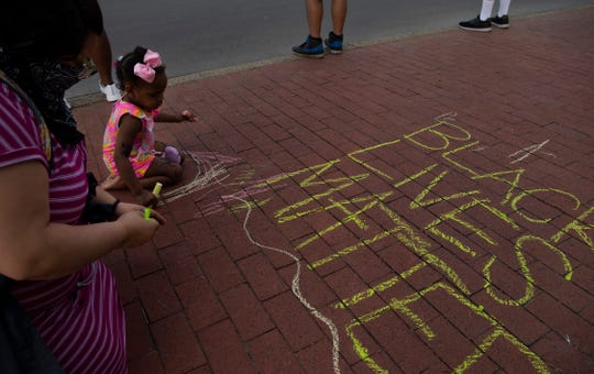 Charlisse Irvine, 2, adds her touches to a chalk sign at a staged protest for George Floyd on Riverside Drive near the Pagoda in Evansville Monday afternoon, June 1, 2020.