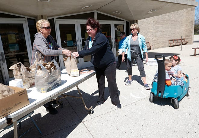 Fond du Lac School Distict's Laurie Schlafer hands Courtney Johnson of Fond du Lac bagged lunches at Riverside Elementary School.