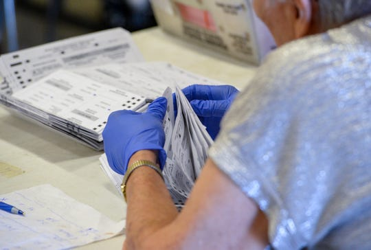 A ballot judge prepares state primary ballots for the counting machine on Tuesday morning in the Exhibition Hall at Montana ExpoPark.