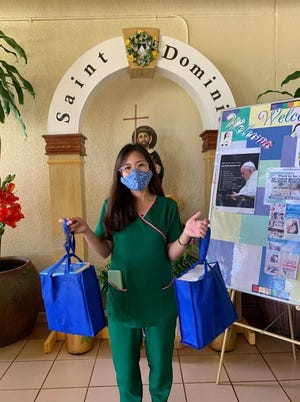 Ruth Alcoran of St. Dominic's Senior Care Home in Barrigada Heights with some of the masks donated by GTA.