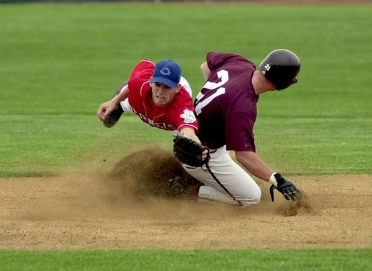 Christian County's Ryan Isom dives for the ball as Henderson County's Aaron Hauser slides into second base during the 2002 Second Region Tournament at Union County High School.