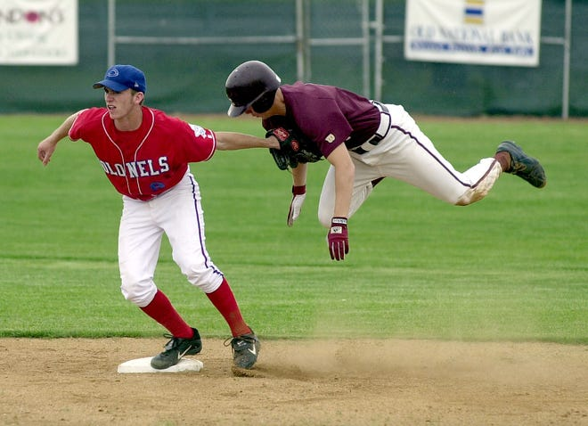 Henderson County's Tanner Siewert goes airborne as he attempts to reach second base, but is tagged out by Christian County shortstop Ryan Isom during the 2002 Second Region Tounament at Union County High School.