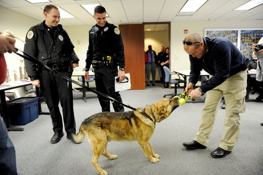 Darrin Phegley / The Gleaner HPD's K-9 dog Santo, center, plays with Det. Shannon Troutman, right, as officer Jared Shehorn, center, and Sgt. Allen Schrecker, left, look on during Santo's retirement party at the police station Thursday afternoon, March 21, 2013. Santo's handler, officer Jason Hargitt, said in Santo's 9 year career he has netted around $500,000 in seizures of drugs, narcotics and vehicles and has located 30 some felons. Santo began at the department in June of 2004 and retired March 13, 2013.
