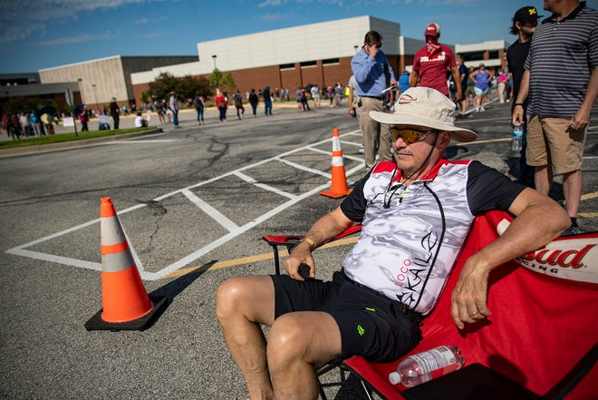Michael O'Connor sits in a lawn chair waiting to vote in the primary election, in a line that snakes through the parking lot and around the building at North Central High School in Indianapolis on Tuesday, June 2, 2020. Several polling locations experienced backups, resulting in several-hour wait times. O'Connor had been in line for about an hour already.