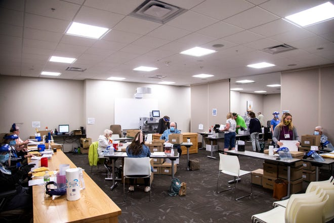 Workers wearing face shields and masks open mail-in primary election ballots during the novel coronavirus pandemic, Monday, June 1, 2020, at the Johnson County Health and Human Services building, in Iowa City, Iowa.