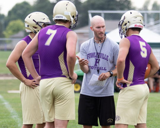 Fowlerville football coach Jon Fletcher works with his quarterbacks on the first day of practice in 2019.